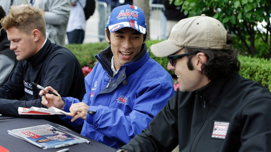 Takuma Sato, of Japan, left, jokes with fellow driver Dario Franchitti, of Scotland, during an autograph session before the public drivers meeting for the Indianapolis 500 auto race at the Indianapolis Motor Speedway in Indianapolis, Saturday, May 25, 2013. (AP Photo/Darron Cummings)