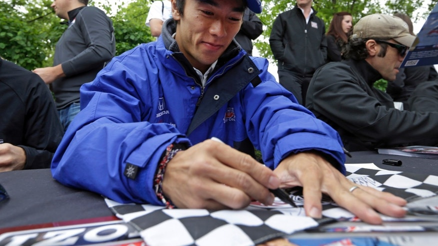 Takuma Sato, of Japan, signs a checkered flag for a fan during an autograph session before the public drivers meeting for the Indianapolis 500 auto race at the Indianapolis Motor Speedway in Indianapolis, Saturday, May 25, 2013. (AP Photo/Darron Cummings)