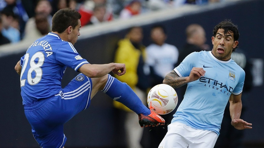 Chelsea defender Cesar Azpilicueta, left, and Manchester City forward Carlos Tevez compete for the ball during the first half of an exhibition international friendly soccer match on Saturday, May 25, 2013, at Yankee Stadium in New York. (AP Photo/Julio Cortez)