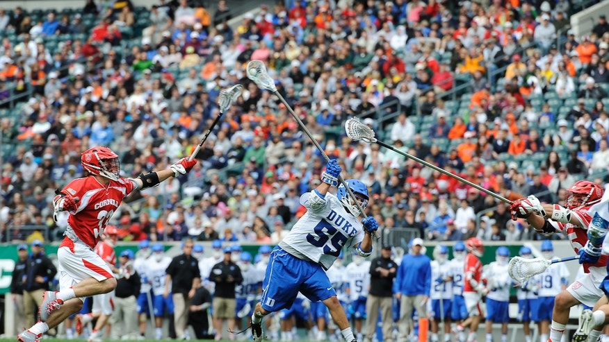 Duke's Bill Conners (55) takes a shots on goal and score while Cornell's Connor Buczek (33) defends during the first half of an NCAA division 1 semifinal lacrosse game on Saturday, May 25, 2013, in Philadelphia. (AP Photo/Michael Perez)