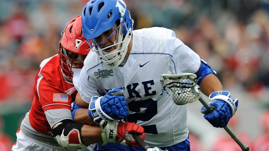 Duke's Greg DeLuca, right, drives past Cornell's Connor Buczek during the first half of an NCAA division 1 semifinal lacrosse game on Saturday, May 25, 2013, in Philadelphia. (AP Photo/Michael Perez)