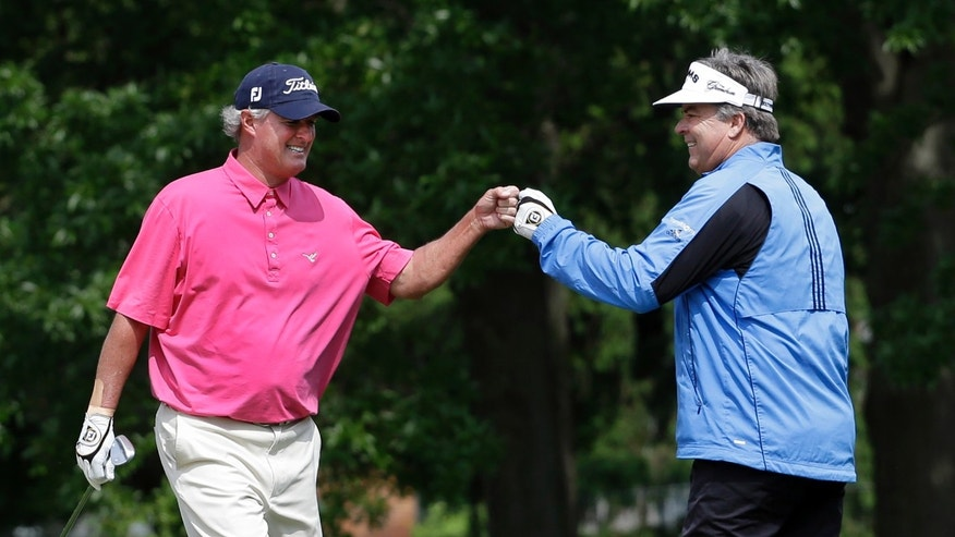 Kenny Perry, right, is congratulated by Russ Cochran after hitting a shot out of a bunker and into the fourth hole for eagle during the third round of the Senior PGA Championship golf tournament at Bellerive Country Club, Saturday, May 25, 2013, in St. Louis. (AP Photo/Jeff Roberson)
