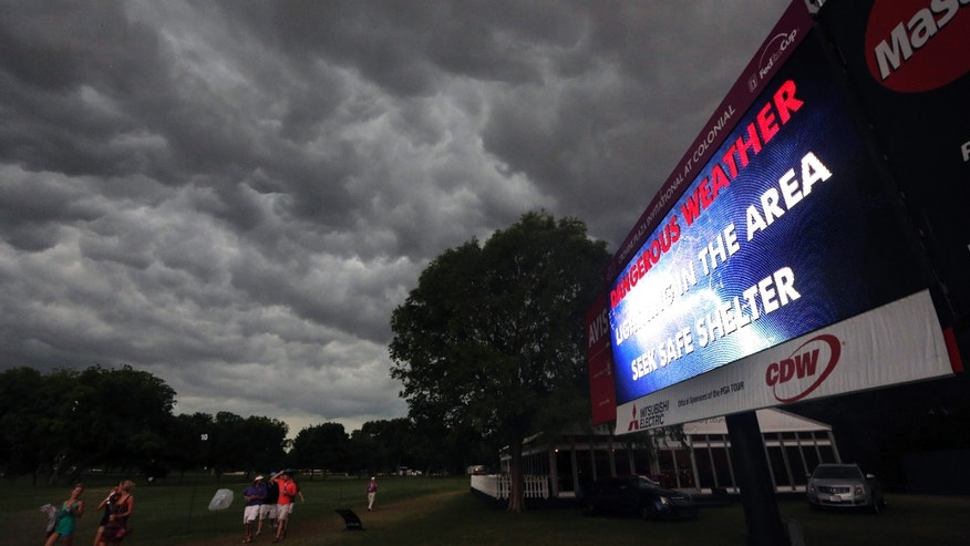 Spectators leave the Colonial Country Club as an incoming storm ends play for the second round of the Colonial golf tournament on Friday, May 24, 2013, in Fort Worth, Texas. (AP Photo/LM Otero)