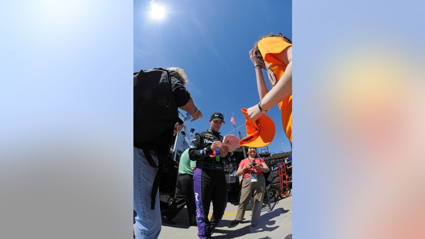 Denny Hamlin signs autographs before practice for Sunday's NASCAR Sprint Cup series Coca-Cola 600 auto race at Charlotte Motor Speedway in Concord, N.C., Saturday, May 25, 2013. (AP Photo/Mike McCarn)