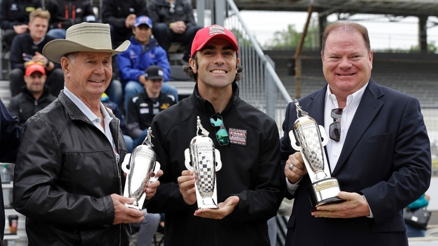 "The 2012 Indy 500 champion Dario Franchitti, of Scotland, center, along with car owner Chip Ganassi, right, and 1963 champion Parnelli Jones receive ""Baby"" Borg-Warner trophies during the public drivers meeting for the Indianapolis 500 auto race at the Indianapolis Motor Speedway in Indianapolis, Saturday, May 25, 2013. (AP Photo/Darron Cummings)"