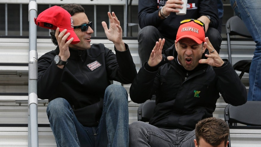 Dario Franchitti, of Scotland, left, and Tony Kanaan, of Brazil, share a story before the start of the public drivers meeting for the Indianapolis 500 auto race at the Indianapolis Motor Speedway in Indianapolis, Saturday, May 25, 2013. (AP Photo/Darron Cummings)