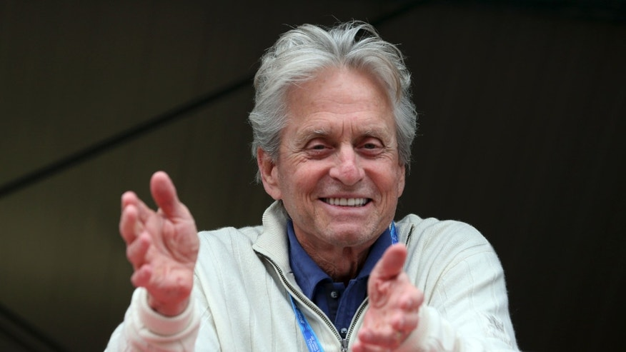 US actor Michael Douglas smiles as he watches from the Ferrari pits during the qualifying session, at the Monaco racetrack in Monaco, Saturday, May 25, 2013. The Formula one race will be held on Sunday. (AP Photo/Luca Bruno)