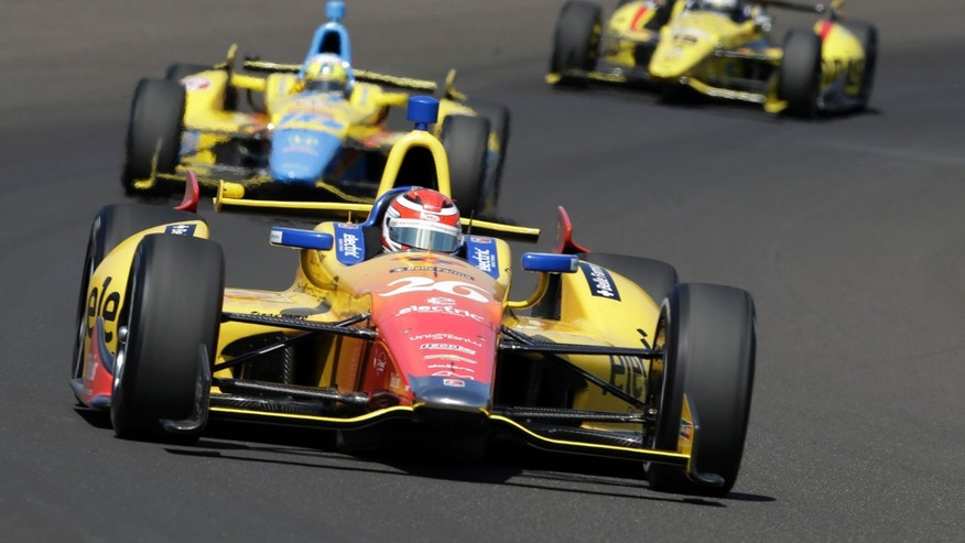 Carlos Munoz, of Colombia, leads a pack through the first turn during the final practice session for the Indianapolis 500 auto race at the Indianapolis Motor Speedway in Indianapolis, Friday, May 24, 2013. (AP Photo/Tom Strattman)