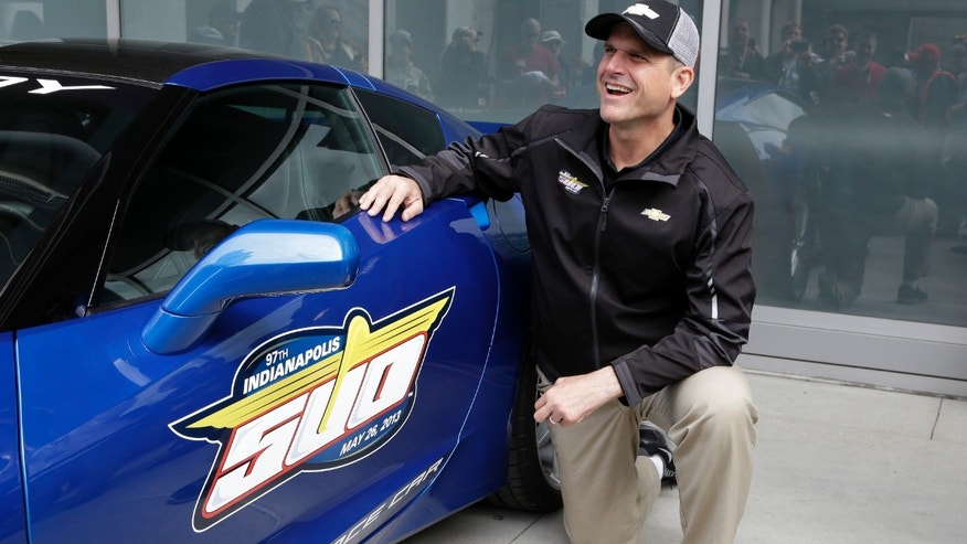 San Francisco 49ers head football coach Jim Harbaugh talks with fans as he poses for photos in Indianapolis, Saturday, May 25, 2013, next to the Chevrolet Corvette Stingray he will drive to lead the field for the start of the Indianapolis 500 auto race at the Indianapolis Motor Speedway on Sunday. (AP Photo/Michael Conroy)