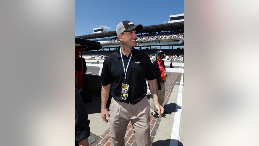 San Francisco 49ers head football coach Jim Harbaugh walks through the pit area during the final practice session for the Indianapolis 500 auto race at the Indianapolis Motor Speedway in Indianapolis, Friday, May 24, 2013. Harbaugh will drive the pace car to start the race. (AP Photo/Darron Cummings)
