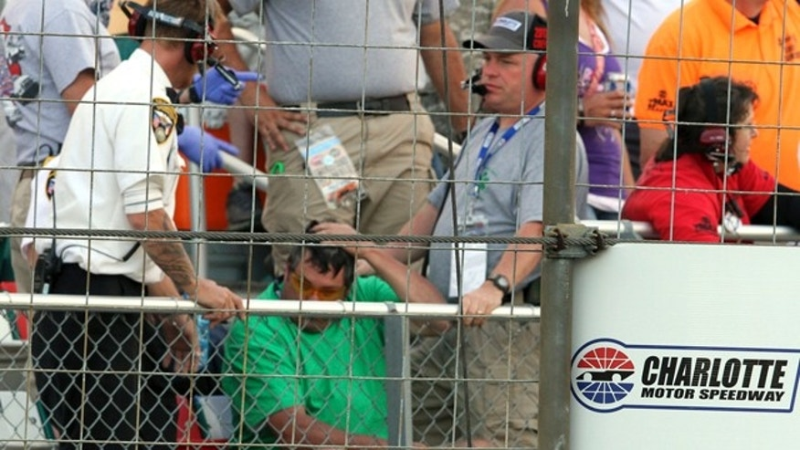 May 26, 2013: Security personnel assist a fan injured by a broken television camera cable during the NASCAR Sprint Cup series Coca-Cola 600 auto race at Charlotte Motor Speedway in Concord, N.C.