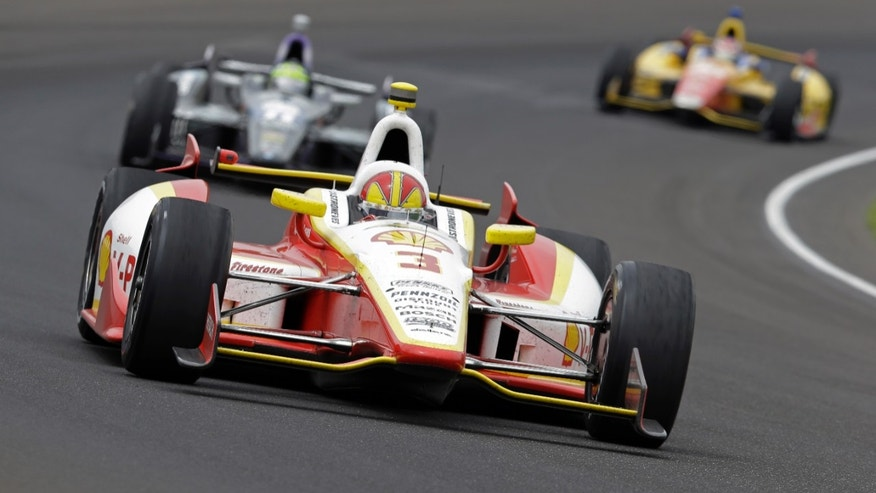 Helio Castroneves, of Brazil, drives through the first turn during the Indianapolis 500 auto race at Indianapolis Motor Speedway in Indianapolis, Sunday, May 26, 2013. (AP Photo/Tom Strattman)