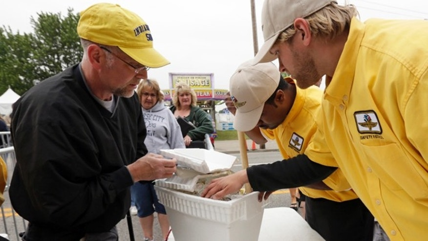 Indianapolis Motor Speedway Safety Patrol members inspect a patron's cooler as he enters the track for the Indianapolis 500 auto race in Indianapolis, Sunday, May 26, 2013. (AP Photo/AJ Mast)