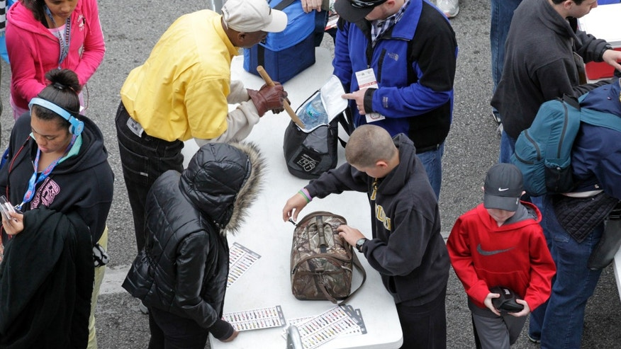Indianapolis Motor Speedway Safety Patrol members inspect patrons' belongings as they enter the track for the Indianapolis 500 auto race in Indianapolis, Sunday, May 26, 2013. (AP Photo/AJ Mast)