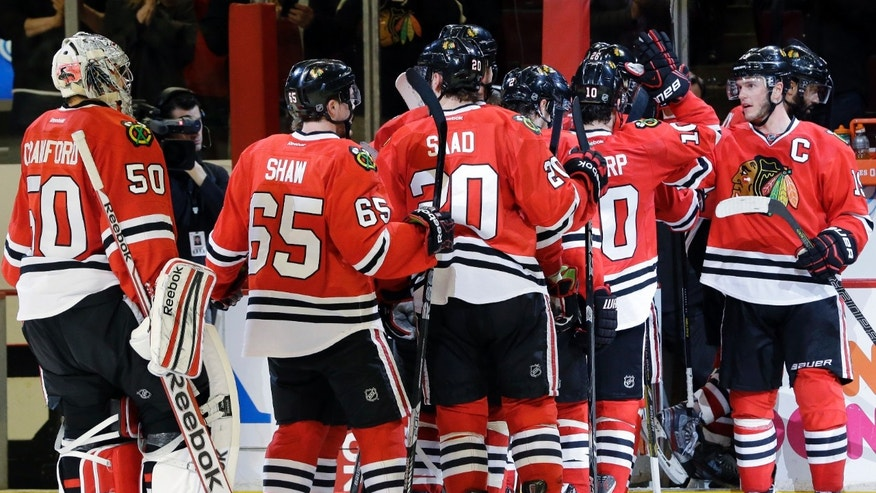 Chicago Blackhawks' Jonathan Toews (19), right, celebrates with teammates after they defeated the Detroit Red Wings 4-1 in Game 5 of the NHL hockey Stanley Cup playoffs Western Conference semifinals in Chicago, Saturday, May 25, 2013. (AP Photo/Nam Y. Huh)