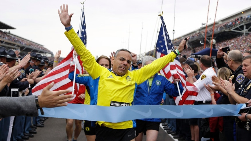 Joe Briseno, of Springfield Ill., leads a group of the approximately 35 runners from the 2013 Boston Marathon, that were unable to finish the race due to the tragic bombings, to complete the distance by crossing finish line at the Indianapolis Motor Speedway before the start of the 97th Indianapolis 500 auto race. (AP Photo/Michael Conroy)