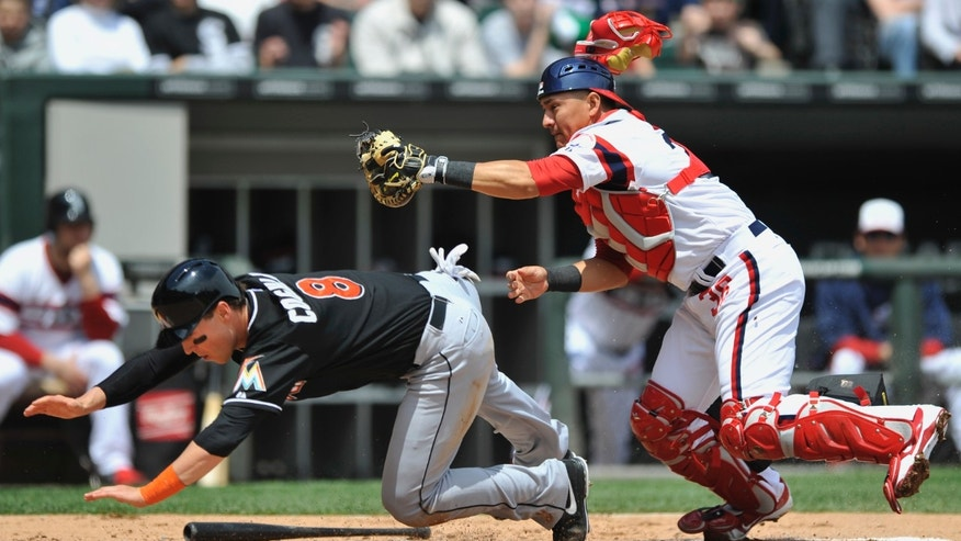 Miami Marlins' Chris Coghlan (8), is tagged out at home plate by Chicago White Sox catcher Hector Gimenez right, after a single by Justin Ruggiano during the second inning of an MLB baseball game in Chicago, Sunday, May 26, 2013. (AP Photo/Paul Beaty)