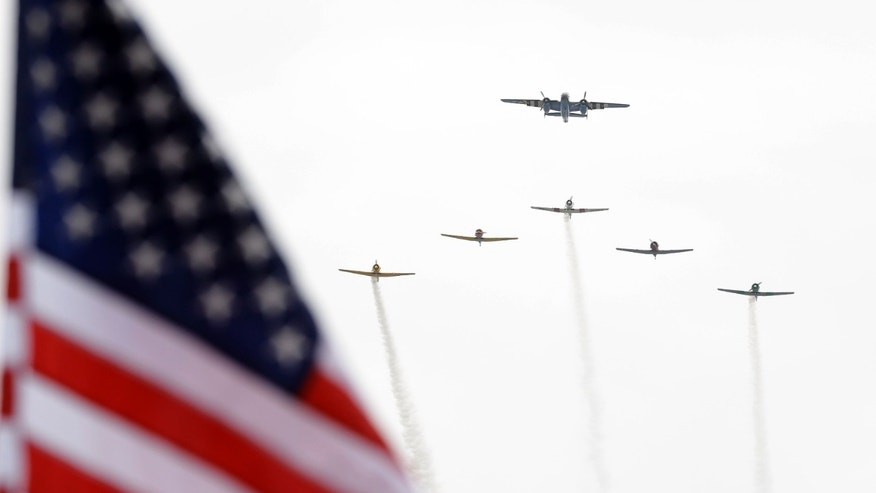 A fly-over of historic war planes during the National Anthem makes it was over the track before the start of the Indianapolis 500 auto race at the Indianapolis Motor Speedway in Indianapolis Sunday, May 26, 2013. (AP Photo/Michael Conroy)