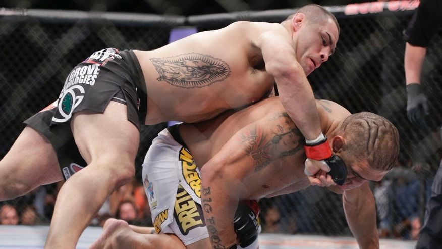 Cain Velasquez, left, lands a punch to the face of Antonio Silva in the first round of the UFC 160 mixed martial arts heavyweight title bout, Saturday, May 25, 2013, in Las Vegas. Velasquez won by technical knockout. (AP Photo/Julie Jacobson)