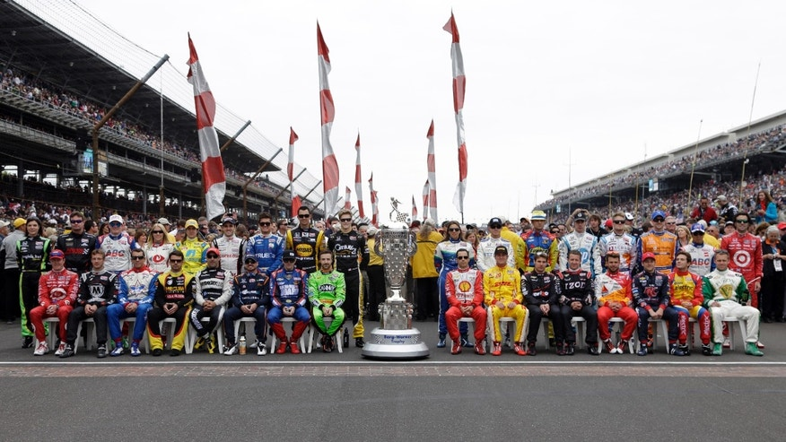 The field for the 97th running of the  Indianapolis 500 auto race poses on the start/finish line before the start of the race at the Indianapolis Motor Speedway in Indianapolis, Sunday, May 26, 2013. (AP Photo/Michael Conroy)
