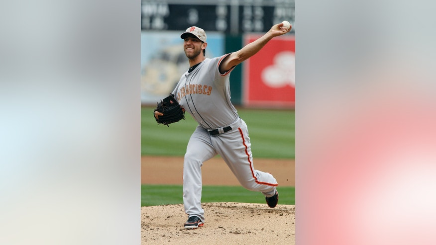 San Francisco Giants starting pitcher Madison Bumgarner  throws to the Oakland Athletics during the first inning of a baseball game in Oakland, Calif., Monday, May 27, 2013. (AP Photo/Tony Avelar)