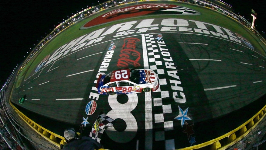 In this photo provided by NASCAR and taken with a fisheye lens, Kevin Harvick takes the checkered flag to win the NASCAR Sprint Cup series Coca-Cola 600 auto race at Charlotte Motor Speedway in Concord, N.C., Sunday, May 26, 2013. (AP Photo/Chris Trotman)