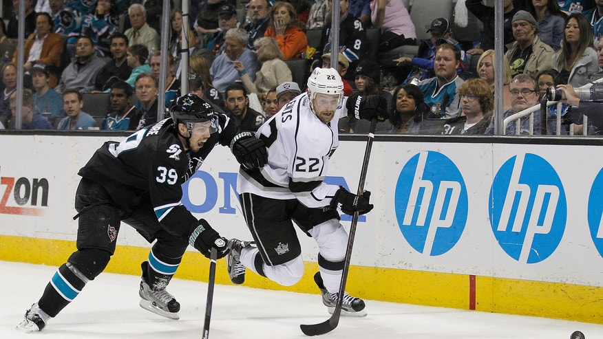 Los Angeles Kings center Trevor Lewis (22) and San Jose Sharks center Logan Couture (39) chase down the puck during the second period in Game 6 of their second-round NHL hockey Stanley Cup playoff series in San Jose, Calif., Sunday, May 26, 2013. (AP Photo/Tony Avelar)