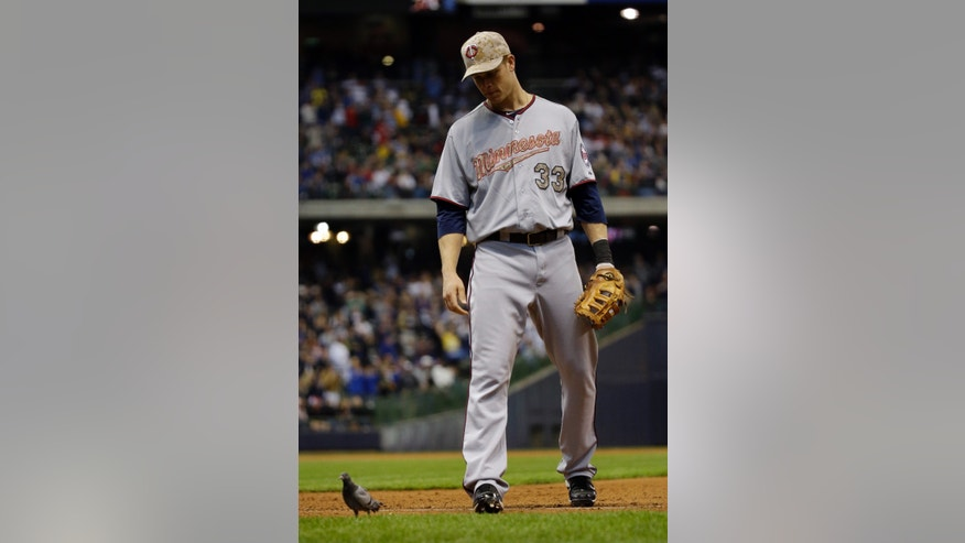 Minnesota Twins first baseman Justin Morneau tries to get a bird away from first base during the sixth inning of a baseball game against the Milwaukee Brewers Monday, May 27, 2013, in Milwaukee. (AP Photo/Morry Gash)