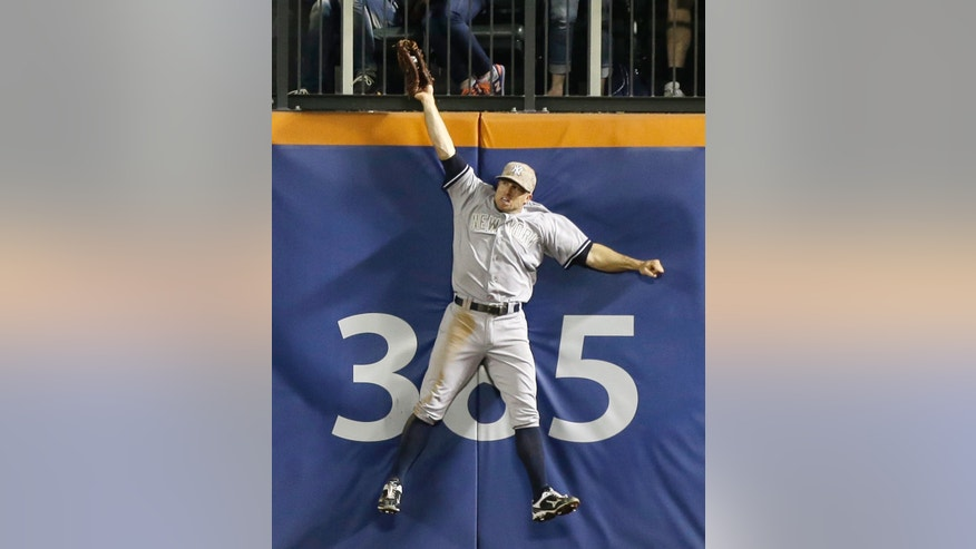 New York Yankees center fielder Brett Gardner (11) catches Daniel Murphy's sixth-inning flyout at the outfield wall for the third out in an interleague baseball game at Citi Field in New York, Monday, May 27, 2013. One runner was on base at the time. (AP Photo/Kathy Willens)