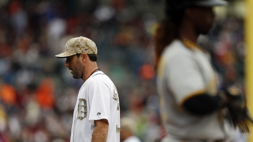 Detroit Tigers starting pitcher Justin Verlander  walks back to the dugout as Pittsburgh Pirates' Andrew McCutchen stands at the plate after striking out during the seventh inning of a baseball game in Detroit, Monday, May 27, 2013. (AP Photo/Carlos Osorio)