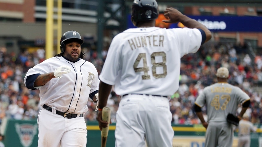 Detroit Tigers' Prince Fielder, left, is met at home plate by teammate right fielder Torii Hunter (48) after they both scored on a double by Tigers designated hitter Victor Martinez during the fifth inning of a baseball game in Detroit, Monday, May 27, 2013. At far right is Pirates starting pitcher Francisco Liriano. (AP Photo/Carlos Osorio)
