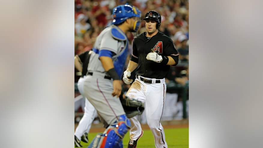 Arizona Diamondbacks' Paul Goldschmidt scores on a base hit by Martin Prado as Texas Rangers catcher Geovany Soto waits for the throw during the first inning of an inter league baseball game, Monday, May 27, 2013, in Phoenix.  (AP Photo/Matt York)
