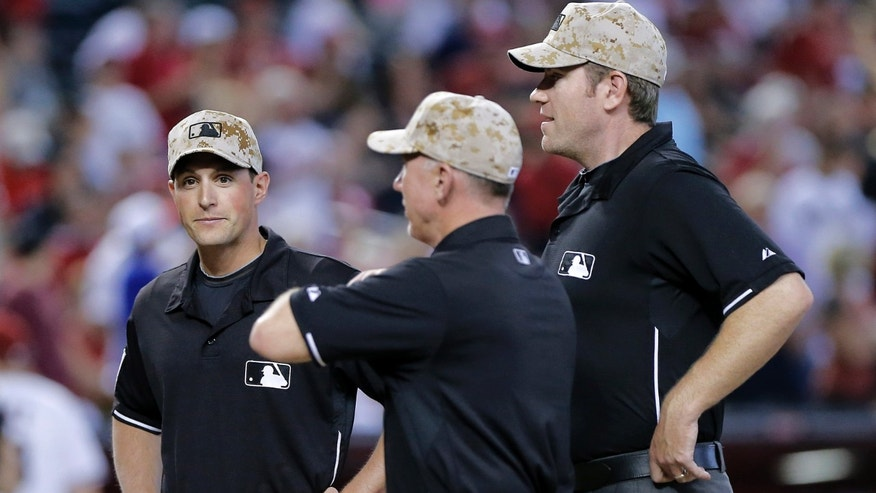 From left; Umpires Quinn Wolcott, Lance Barksdale and Chris Conroy wear camouflage hats for Memorial Day prior to an Arizona Diamondbacks and Texas Rangers nter league baseball game, Monday, May 27, 2013, in Phoenix.  (AP Photo/Matt York)