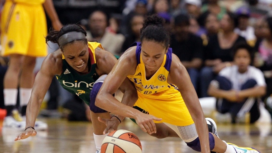 Seattle Storm guard Temeka Johnson, left, and Los Angeles Sparks guard Kristi Toliver scrum on the floor in the first half of a WNBA basketball game in Los Angeles, Sunday, May 26, 2013. (AP Photo/Reed Saxon)