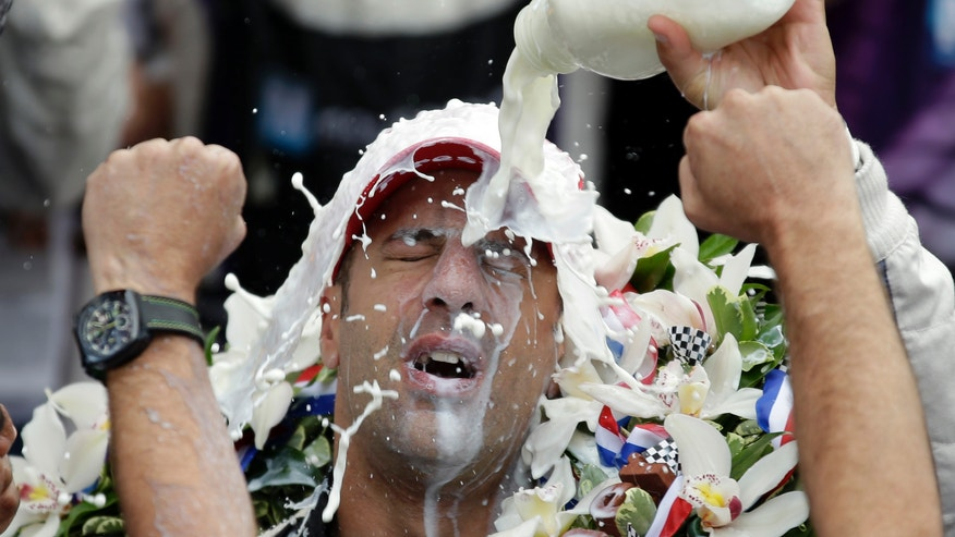 Tony Kanaan, of Brazil, celebrates by pouring the winners milk over his heads after winning the Indianapolis 500 auto race at the Indianapolis Motor Speedway in Indianapolis, Sunday, May 26, 2013. (AP Photo/Michael Conroy)