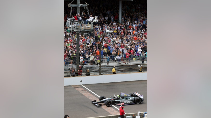 Tony Kanaan, of Brazil, celebrates as he crosses the finish line to win the Indianapolis 500 auto race at Indianapolis Motor Speedway in Indianapolis, Sunday, May 26, 2013. (AP Photo/Dave Parker)