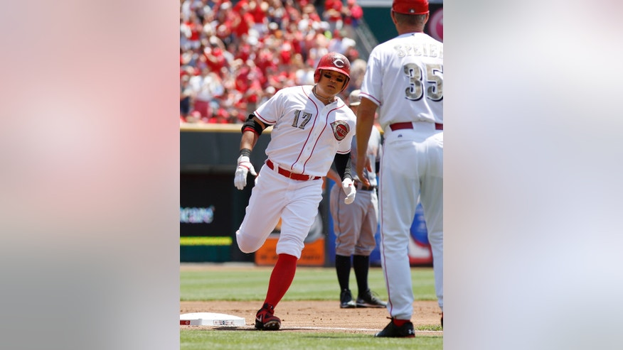 Cincinnati Reds center fielder Shin-Soo Choo, left, is congratulated by third base coach Chris Speier, right, in the first inning during a baseball game, Monday, May 27, 2013, in Cincinnati. (AP Photo/David Kohl)