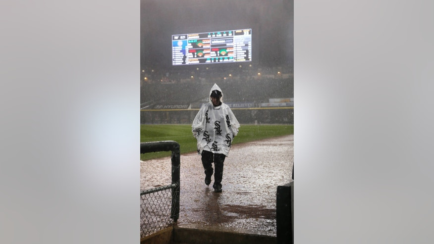 A security guard heads for shelter as heavy rain and hail brings a halt to an interleague baseball game between the Chicago White Sox and the Chicago Cubs in the third inning Tuesday, May 28, 2013, in Chicago. (AP Photo/Charles Rex Arbogast)