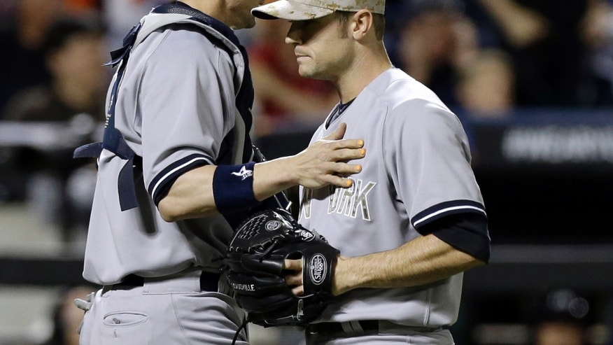 New York Yankees catcher Chris Stewart (19) consoles New York Yankees relief pitcher David Robertson after Robertson allowed an RBI single to New York Mets Daniel Murphy in an interleague baseball game at Citi Field in New York, Monday, May 27, 2013. (AP Photo/Kathy Willens)
