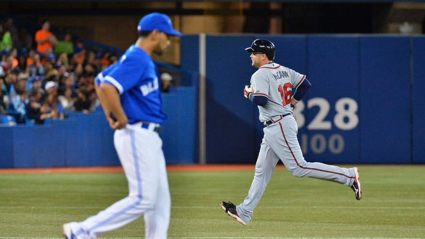 Atlanta Braves' Brian McCann, right, rounds the bases past Toronto Blue Jays pitcher Ramon Ortiz, left, after hitting a solo home run during the sixth inning of an interleague baseball game in Toronto on Tuesday, May 28, 2013. (AP Photo/The Canadian Press, Nathan Denette)