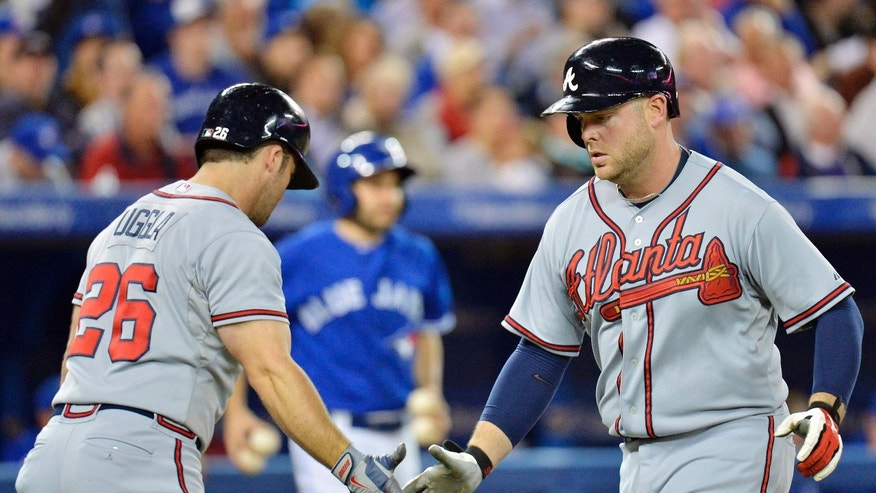 CORRECTS TO SOLO HOME RUN - Atlanta Braves designated hitter Brian McCann, right, is greeted by teammate Dan Uggla, left, after hitting a solo home against the Toronto Blue Jays during the sixth inning of an interleague baseball game in Toronto on Tuesday, May 28, 2013. McCann hit two home runs, including a solo shot in the 10th inning that lifted the Braves over the Blue Jays 7-6 on Tuesday. (AP Photo/The Canadian Press, Nathan Denette)