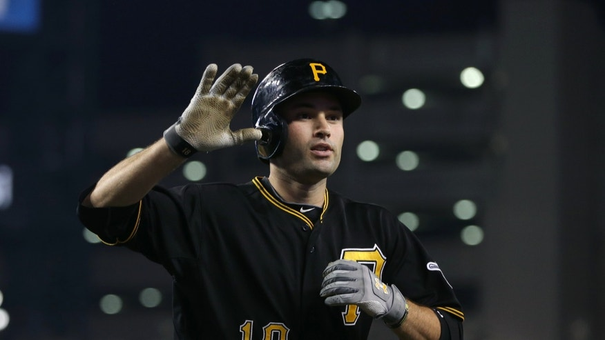 Pittsburgh Pirates second baseman Neil Walker arrives at the dugout after hitting a solo home run during the 11th inning of an interleague baseball game against the Detroit Tigers in Detroit, Tuesday, May 28, 2013. (AP Photo/Carlos Osorio)
