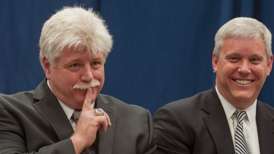"Dennis ""Red"" Gendron, left, gestures animatedly during a press conference where he was introduced as the new men's hockey coach by Athletic Director Steve Abbott, right, at the University of Maine, Tuesday, May 28, 2013, in Orono, Maine.  (AP Photo/Michael C. York)"