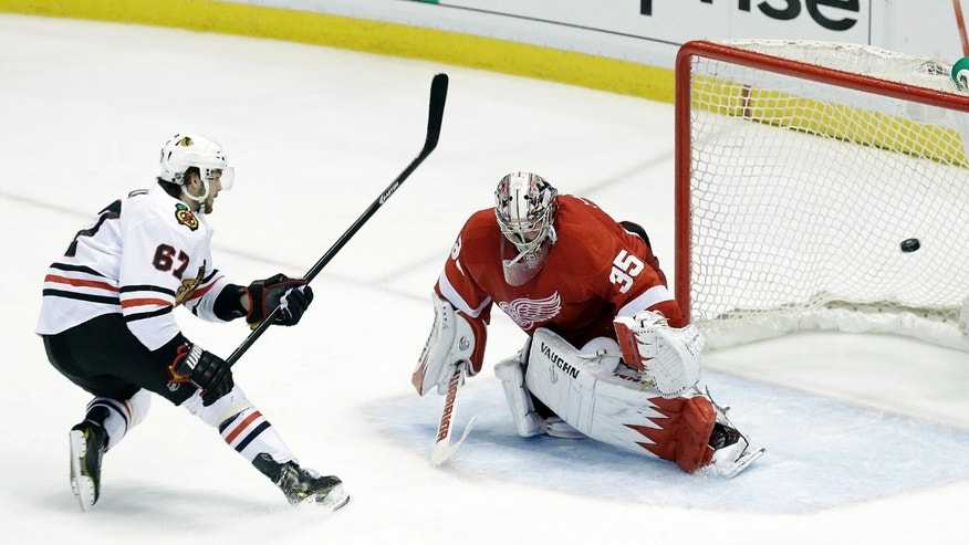 Chicago Blackhawks center Michael Frolik (67), of the Czech Republic, scores a penalty shot goal against the Detroit Red Wings goalie Jimmy Howard (35) during the third period in Game 6 of the Western Conference semifinals in the NHL hockey Stanley Cup playoffs in Detroit, Monday, May 27, 2013. (AP Photo/Paul Sancya)