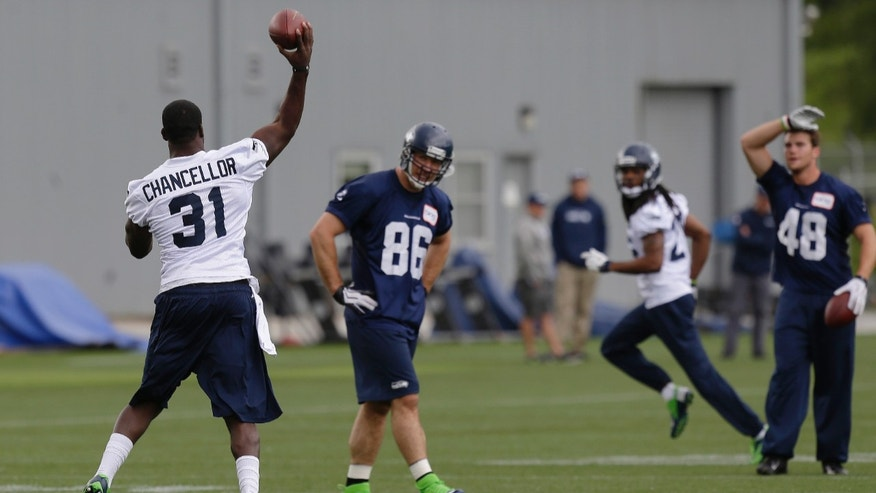 Seattle Seahawks strong safety Kam Chancellor (31) throws a pass to cornerback Richard Sherman as teammates watch, Tuesday, May 28, 2013, during the NFL football team's practice in Renton, Wash. (AP Photo/Ted S. Warren)