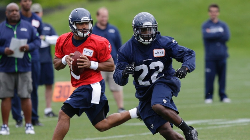 Seattle Seahawks quarterback Russell Wilson, left, looks to pass as running back Robert Turbin (22) provides protection during drill at NFL football practice Tuesday, May 28, 2013, in Renton, Wash. (AP Photo/Ted S. Warren)