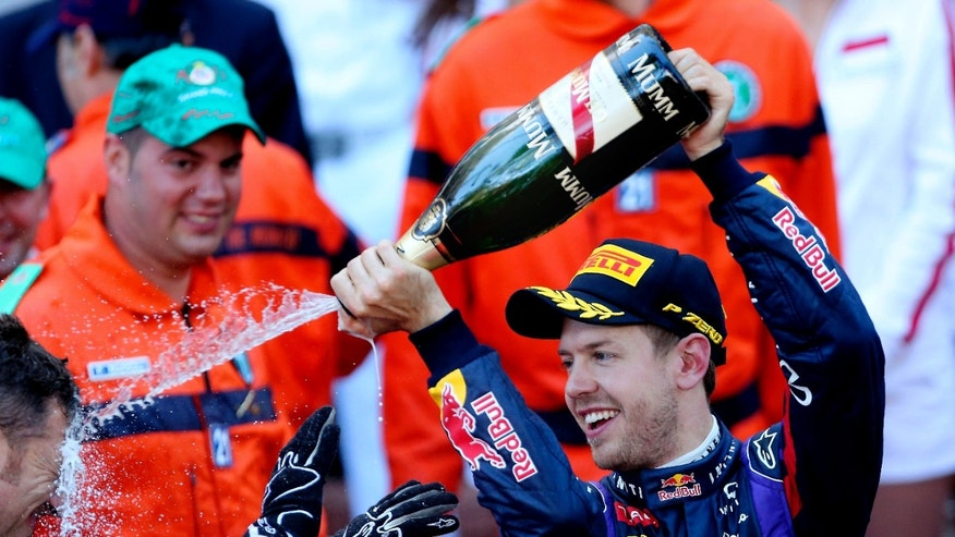 Red Bull driver Sebastian Vettel, of Germany, celebrates after taking a second place during the Formula One Grand Prix at the Monaco racetrack, in Monaco, Sunday, May 26, 2013. (AP Photo/Antonio Calanni)