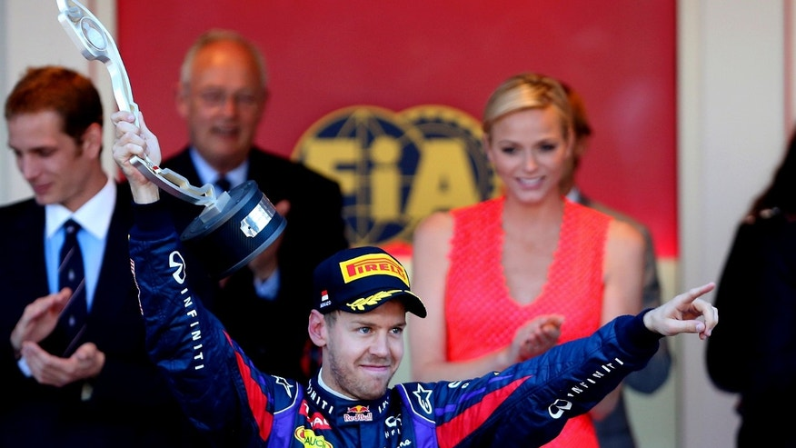 Red Bull driver Sebastian Vettel, of Germany, celebrates on the podium after taking a second place during the Formula One Grand Prix at the Monaco racetrack, in Monaco, Sunday, May 26, 2013. (AP Photo/Antonio Calanni)