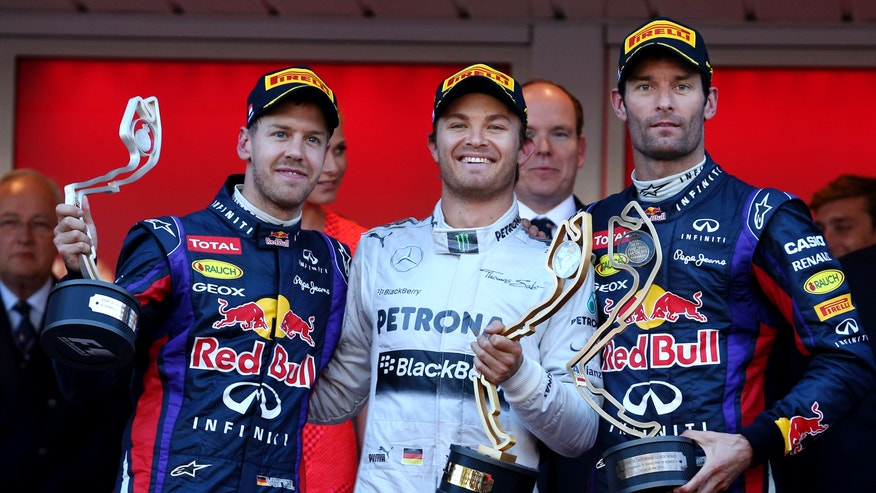 Mercedes driver Nico Rosberg of Germany, winner, at center, Red Bull driver Sebastian Vettel of Germany, second place, and Red Bull driver Mark Webber of Australia, third place, pose on the podium after the Formula One Grand Prix at the Monaco racetrack, in Monaco, Sunday, May 26, 2013. (AP Photo/Luca Bruno)