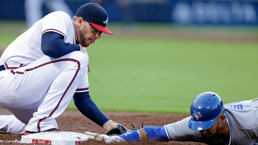 Atlanta Braves' Freddie Freeman, left, is late tagging Toronto Blue Jays' Emilio Bonifacio as he dives back to first base after leading off in the the second inning of a baseball game, Wednesday, May 29, 2013, in Atlanta. (AP Photo/David Goldman)